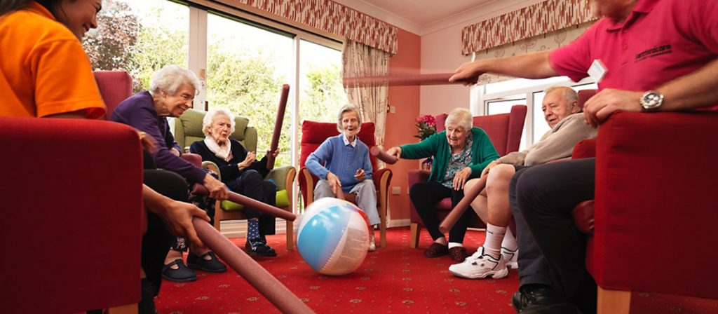 a group of residents sat playing indoor ball games