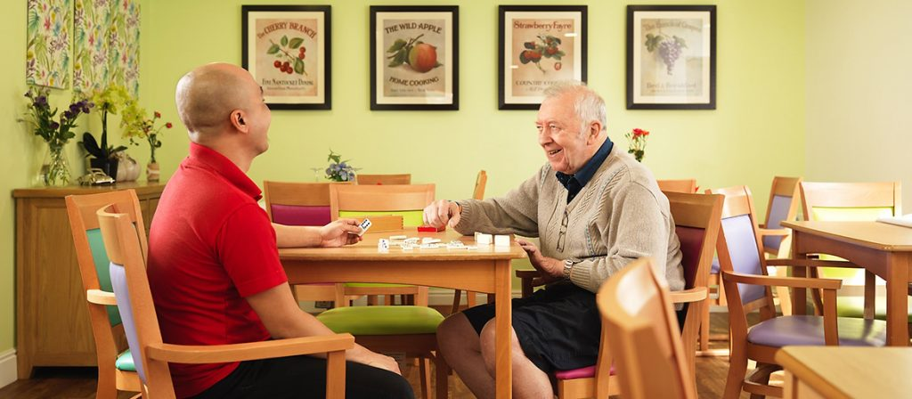 Resident sat at dinning table with a care assistant playing dominoes