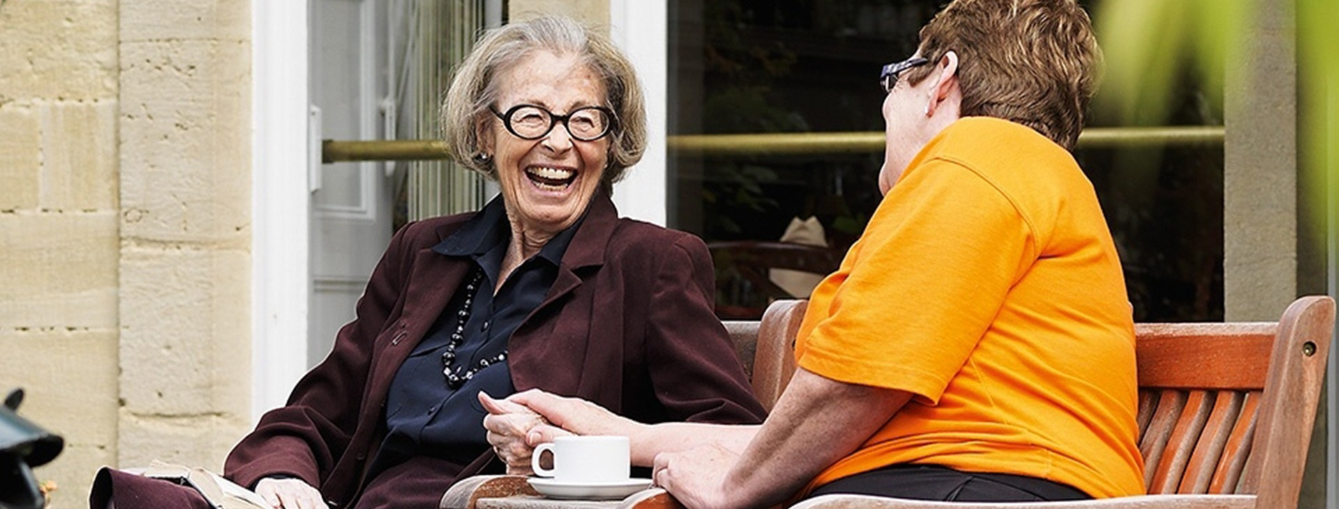 Resident and careworker on a bench laughing