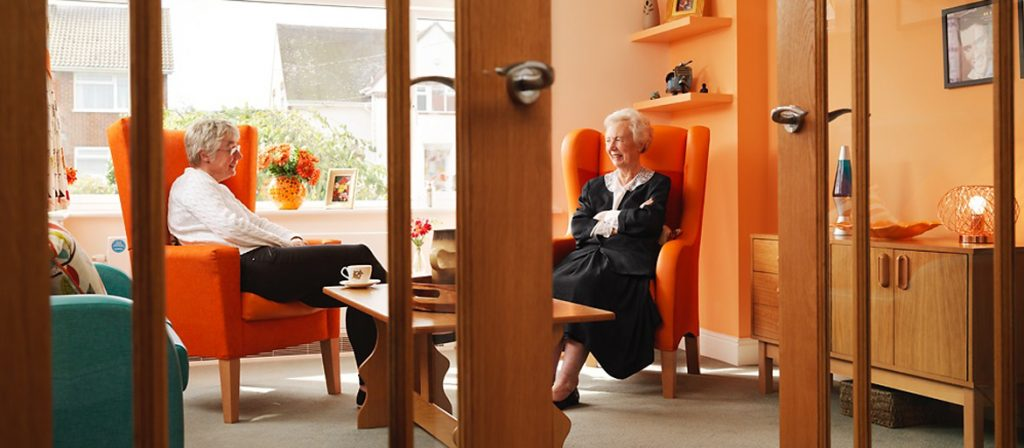 Two residents sat chatting in comfortable orange armchairs