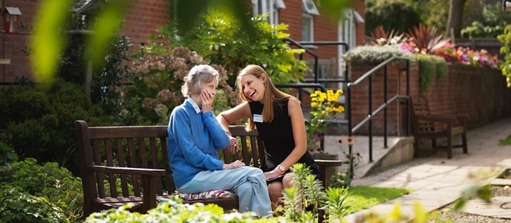 Care home manager sat on a bench laughing with resident in the garden