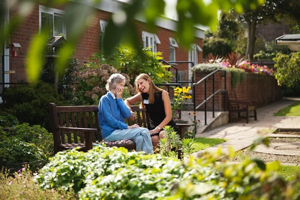 Home manager and resident sat talking on a bench in the grounds