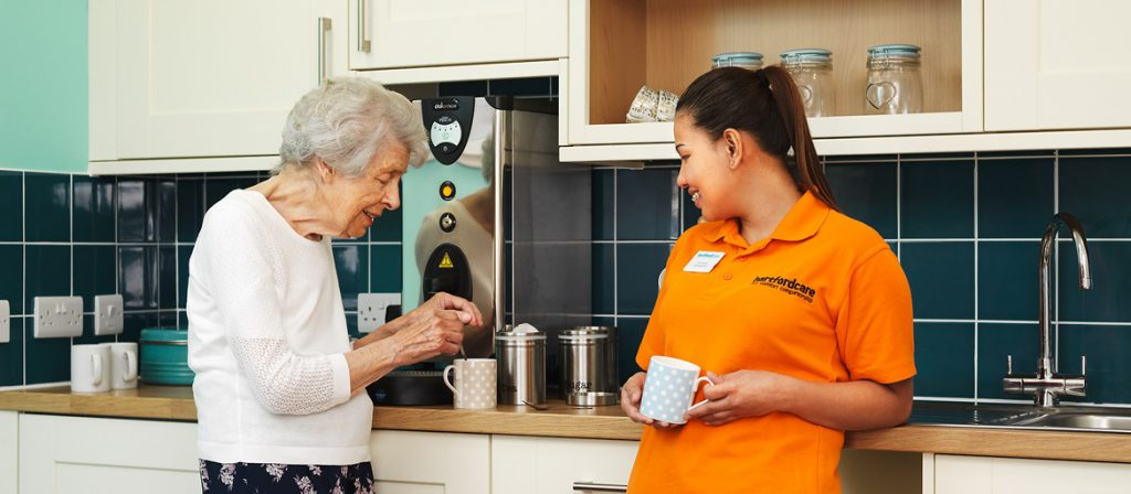 Resident making herself a cup of tea whilst chatting to care assistant