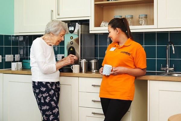 Staff and resident making tea together n the kitchen