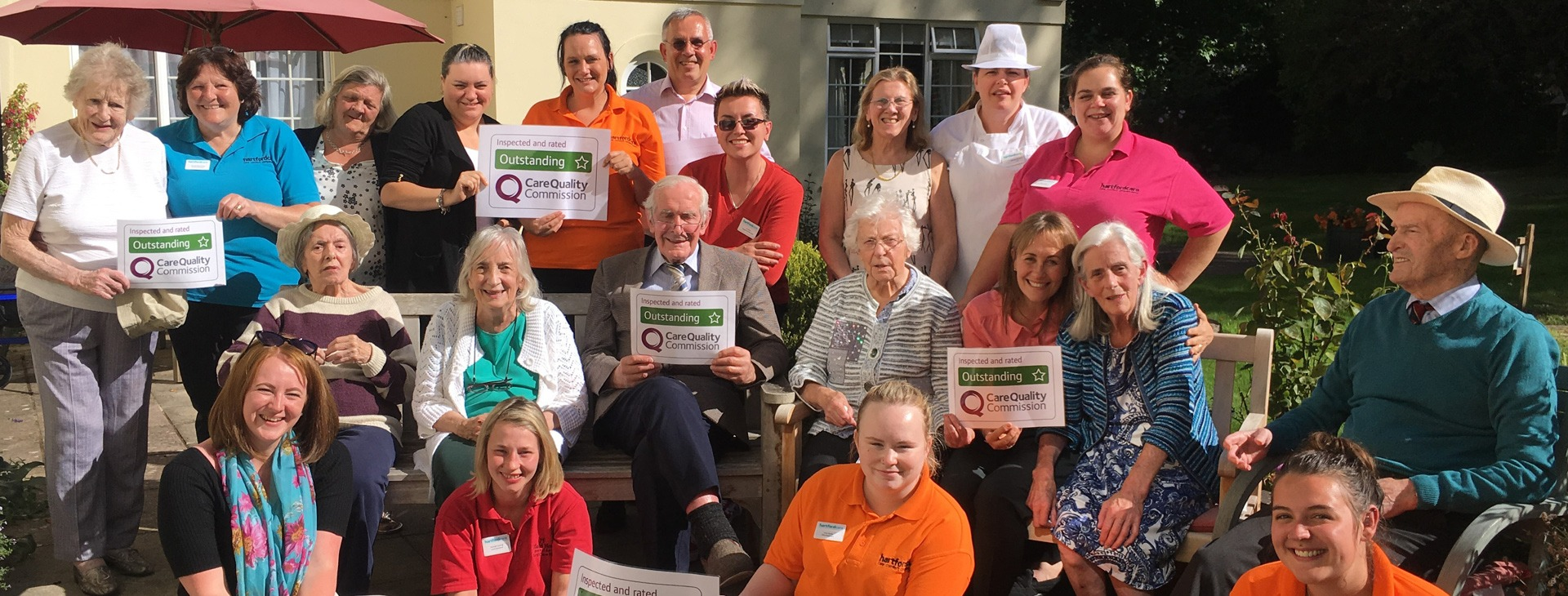 Tegfield staff and residents celebrating outstanding CQC result in the garden