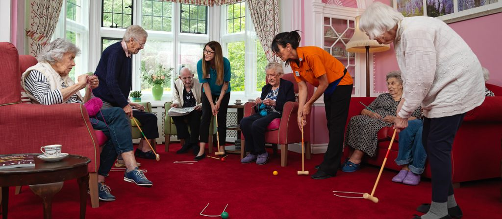 Several residents and staff playing indoor croquet