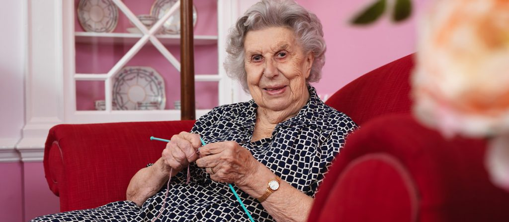 Resident knitting in cosy chair at Woodlands House