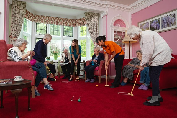 Residents and staff playing indoor croquet in the living room