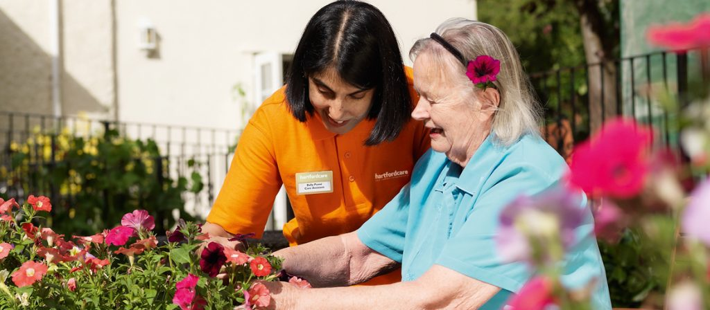 Resident and Carer tending to the flower beds in the garden