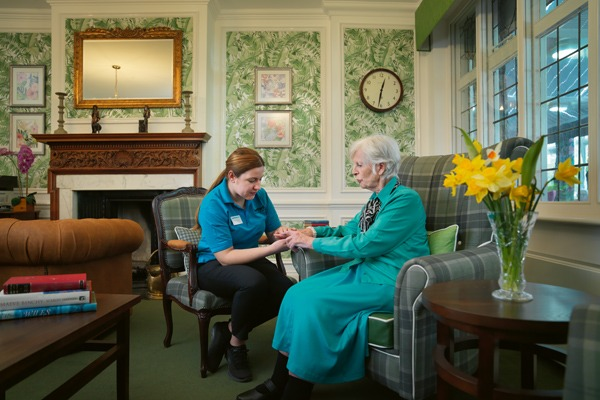 Nurse assessing residents hand whilst sat in a chair