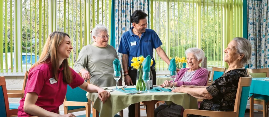 Residents and carers sat around a table in the dinning room all laughing and smiling
