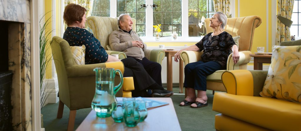 three residents sat chatting in the main lounge