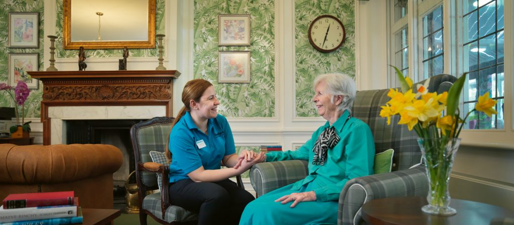 Career tending to a resident whilst sat in the reception area