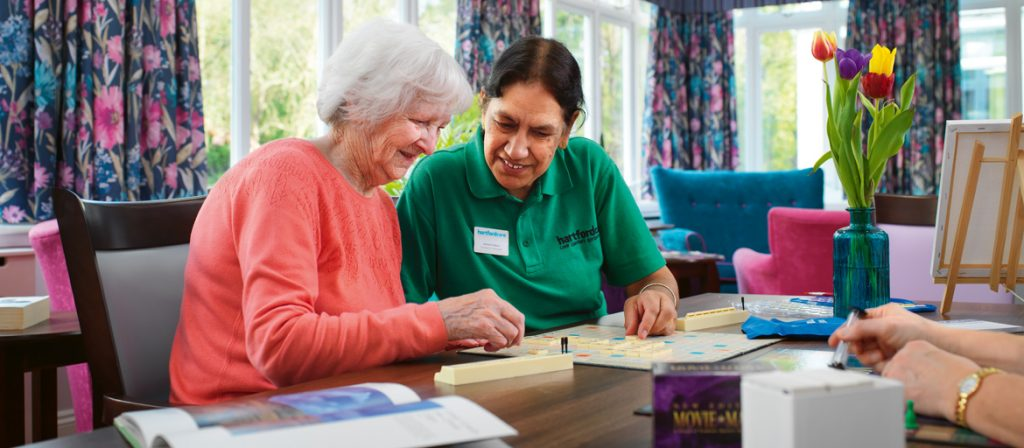 Carer and resident playing scrabble together at the table in the activities room
