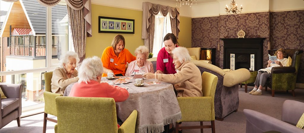 four female residents enjoying afernoon tea in the lounge with two carers on hand to help them