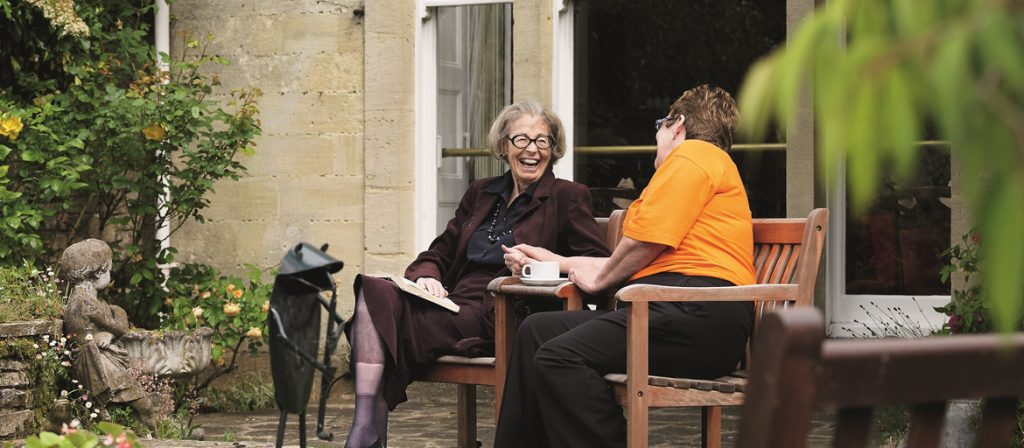 Resident and Carer lauging on a bench in the courtyard of Newland House
