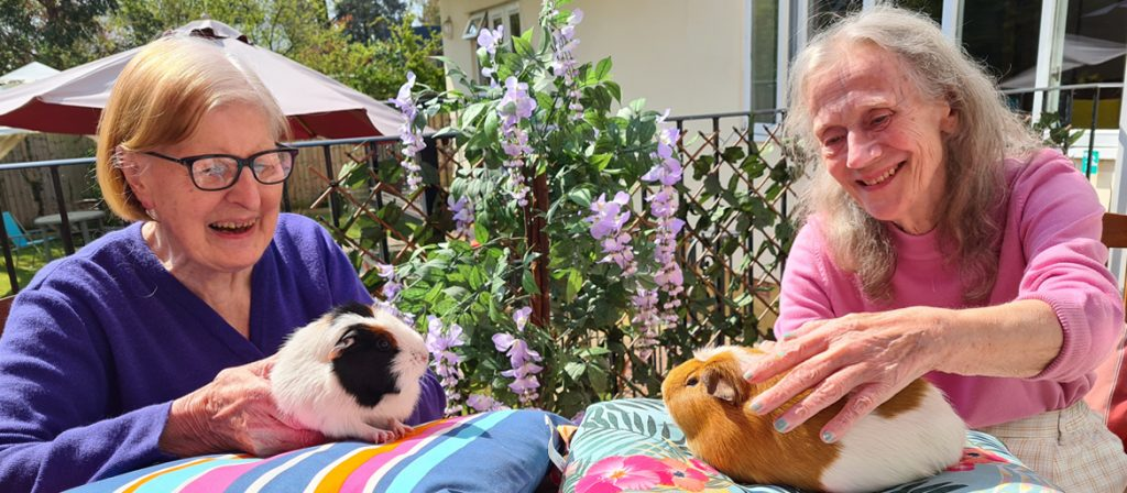 Resident's petting two pet guinea pigs