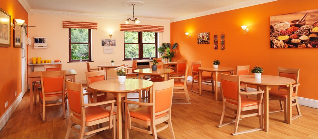 large dinning area with plenty of seating and a warm orange backdrop