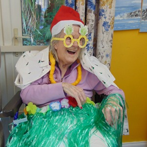 Happy resident celebrating Julymas with Christmas hat and grass skirt