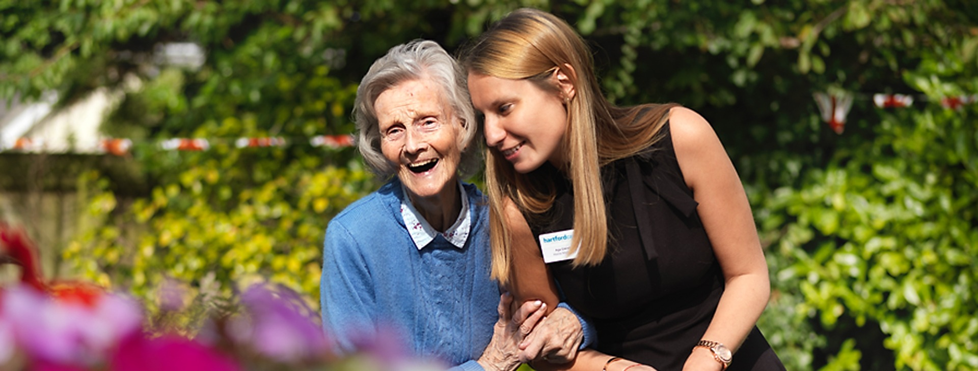 Resident laughing in the garden and linking arms with the home manager